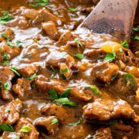 closeup shot of beef tips with gravy in a pot with a wooden spoon inside