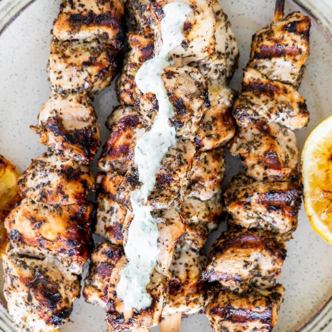 closeup overhead shot chicken souvlaki skewers with a little tzatziki on a plate