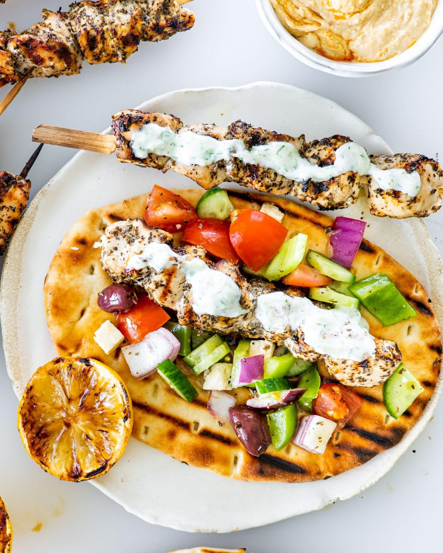chicken souvlaki on a pita bread with tzatziki and some greek salad