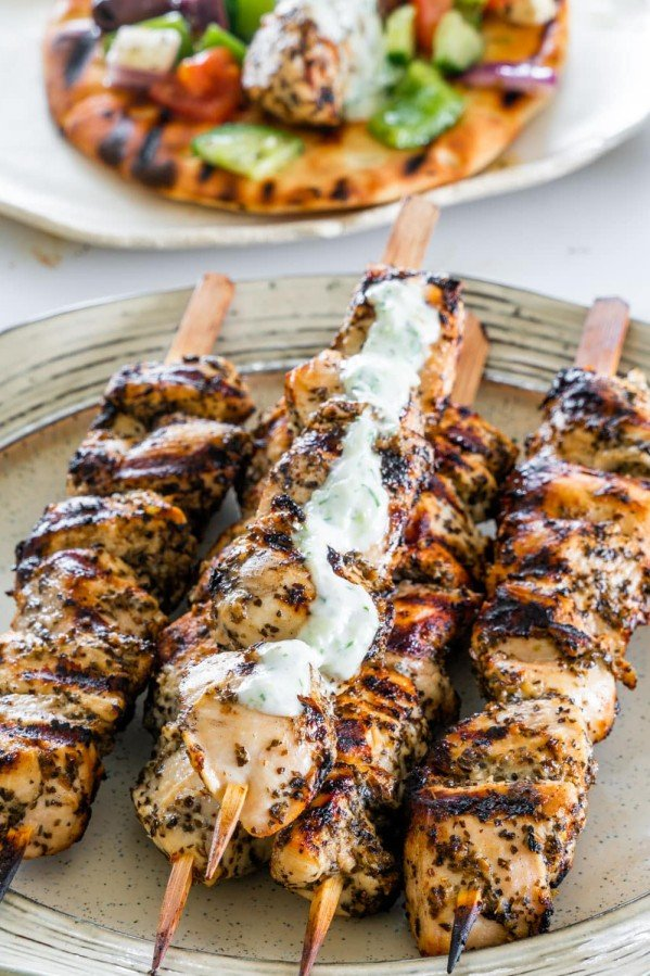 side view shot chicken souvlaki skewers with a little tzatziki on a plate