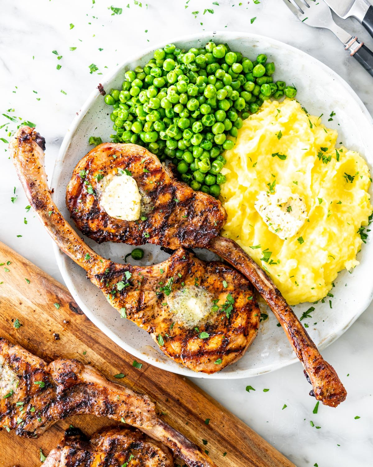overhead shot of grilled pork chops on a plate with mashed potatoes and peas