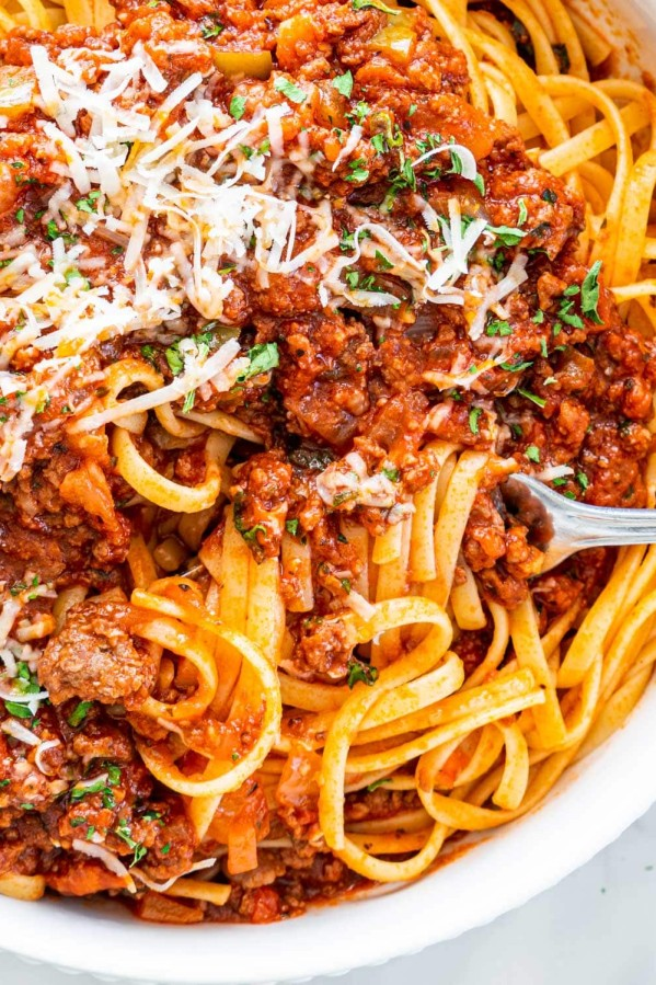 overhead closeup shot of meat sauce over a bed of linguini with a fork twisting some pasta garnished with parmesan cheese and parsley