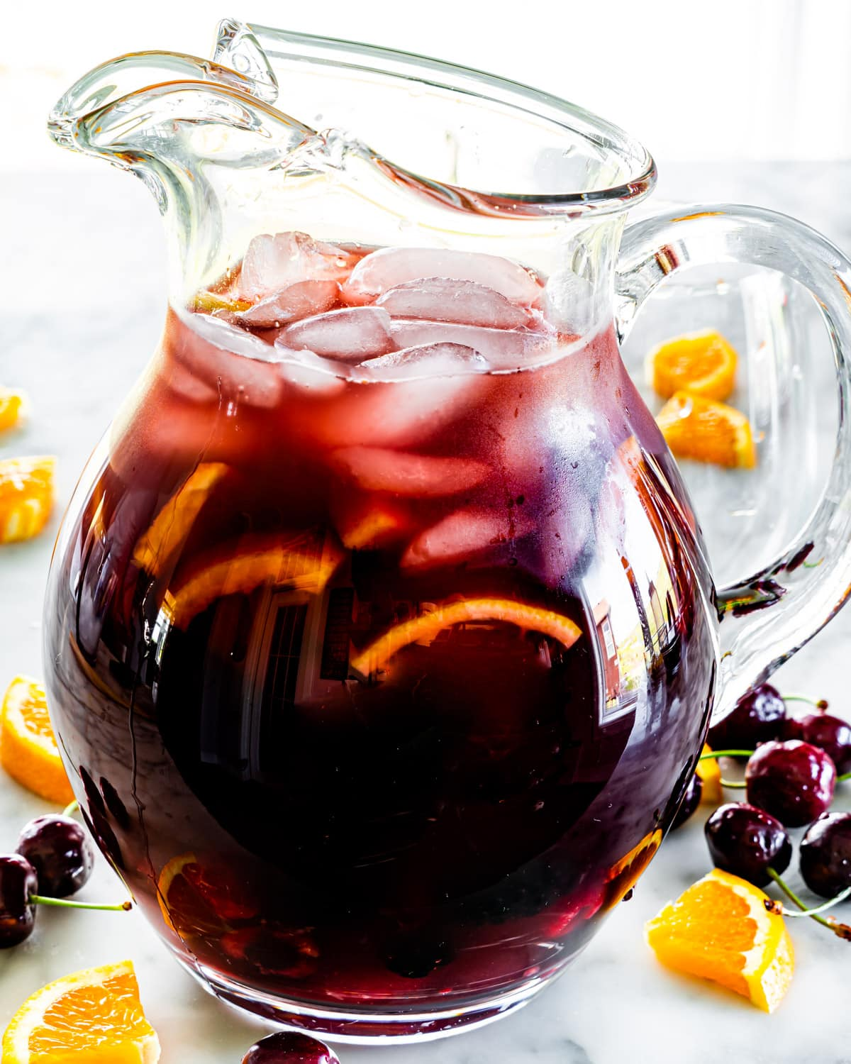 side view shot of a pitcher of red sangria with lots of cherries and orange slices around it