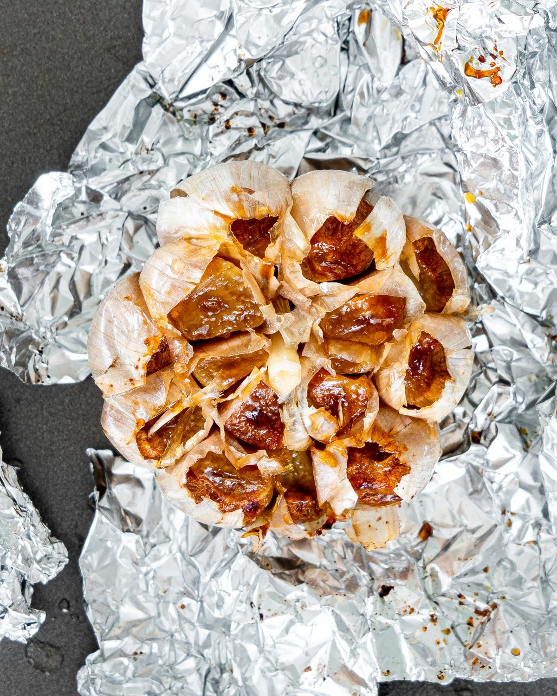 overhead shot of a roasted garlic head on aluminum foil