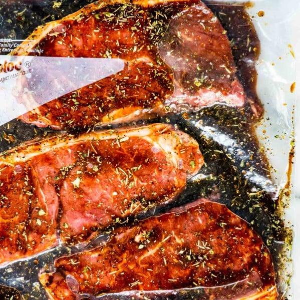 overhead shot of 3 steaks in a marinade in a ziploc bag