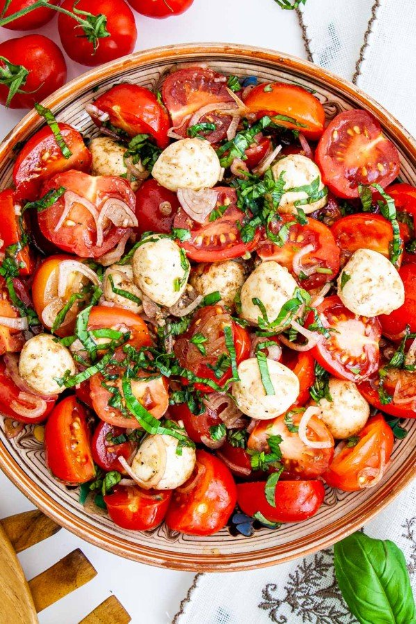 overhead shot of tomato basil salad with bocconcini in a bowl