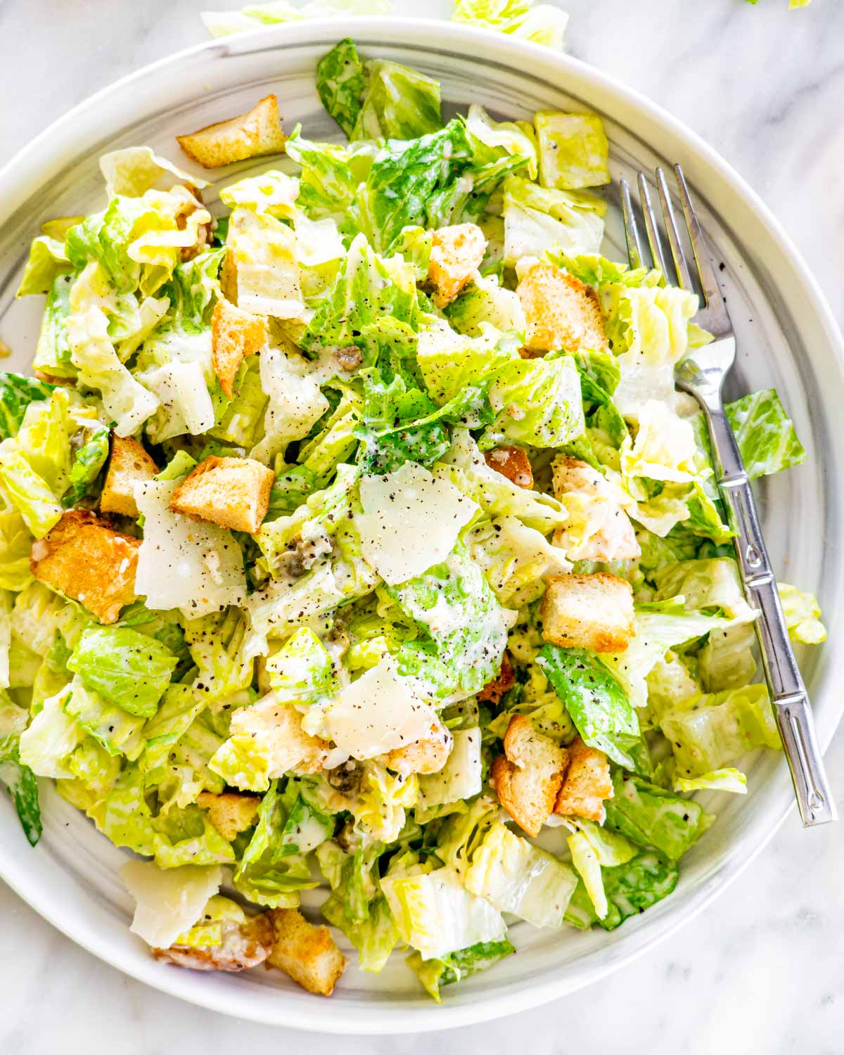 overhead shot of freshly made caesar salad on a plate with a fork in it