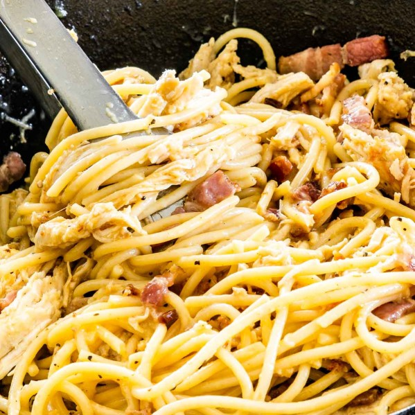 sideview shot of carbonara with chicken and bacon in a black skillet with a pair of tons in it
