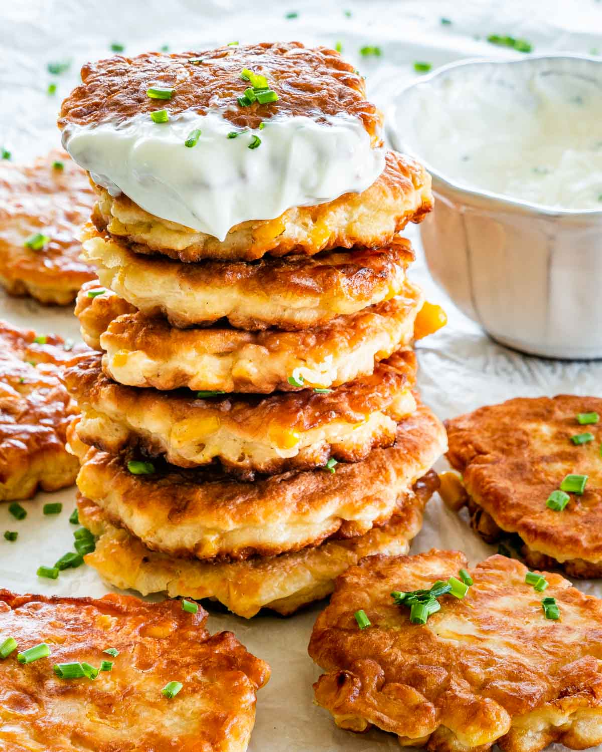 a stack of corn fritters garnished with some chives and a little bowl of sour cream in the background