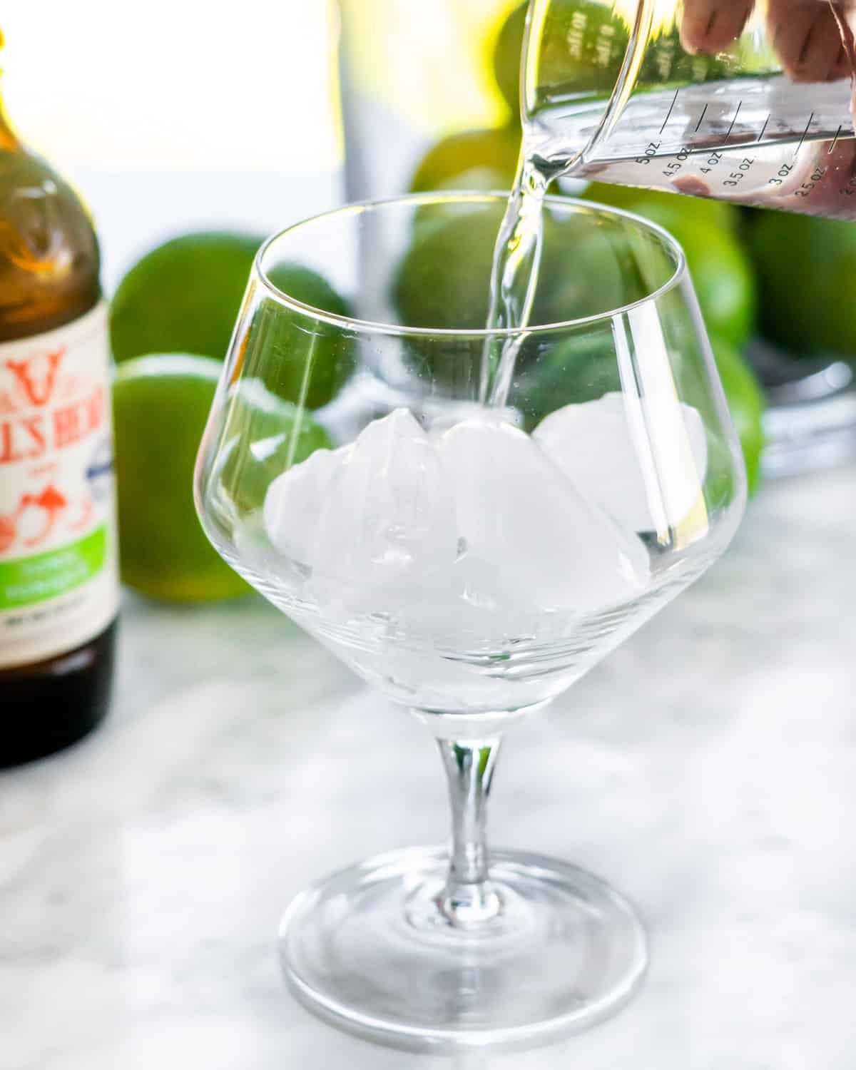 a hand pouring gin into a glass with ice