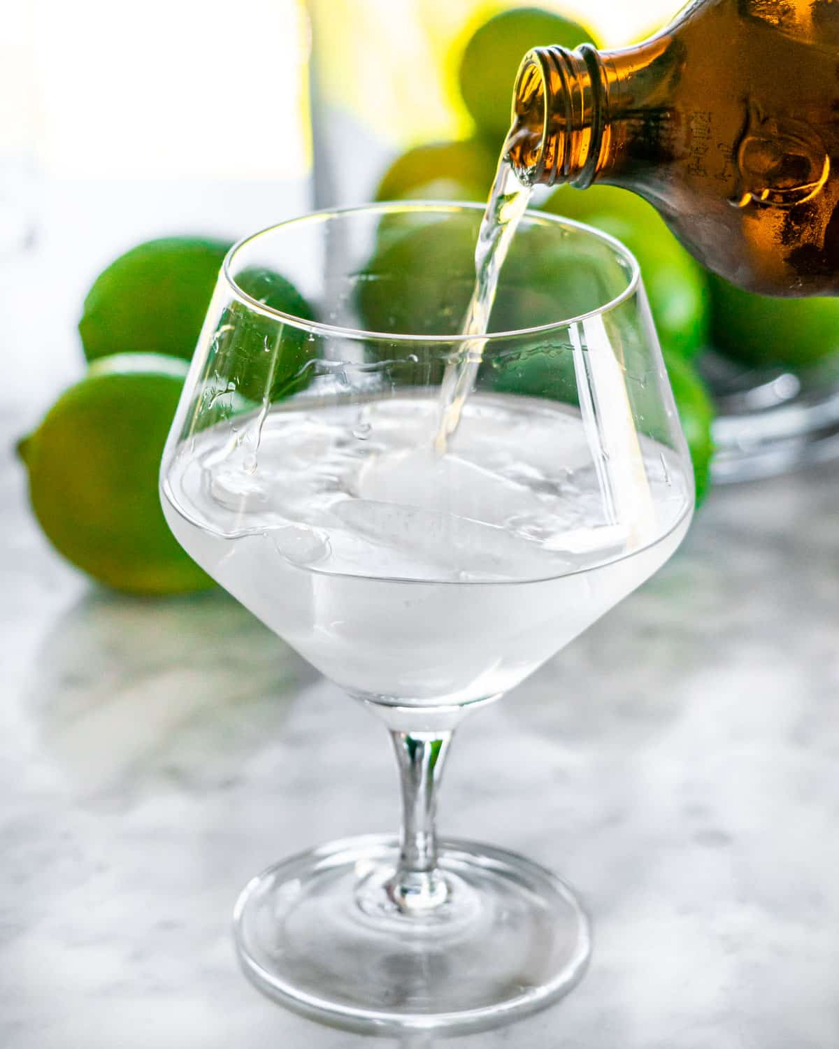 a hand pouring tonic water in a glass with ice and gin