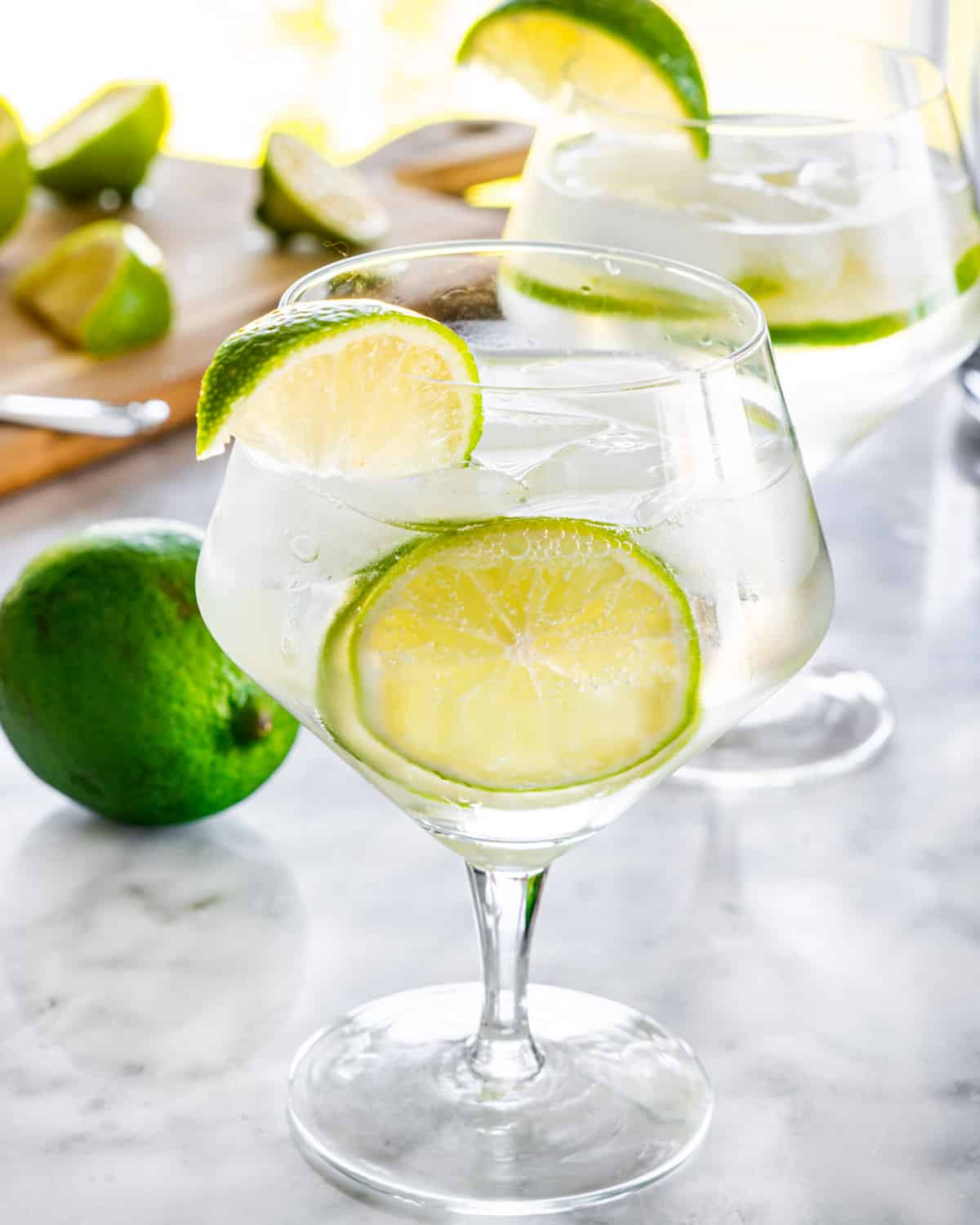 two gin and tonic glasses garnished with lime wedges