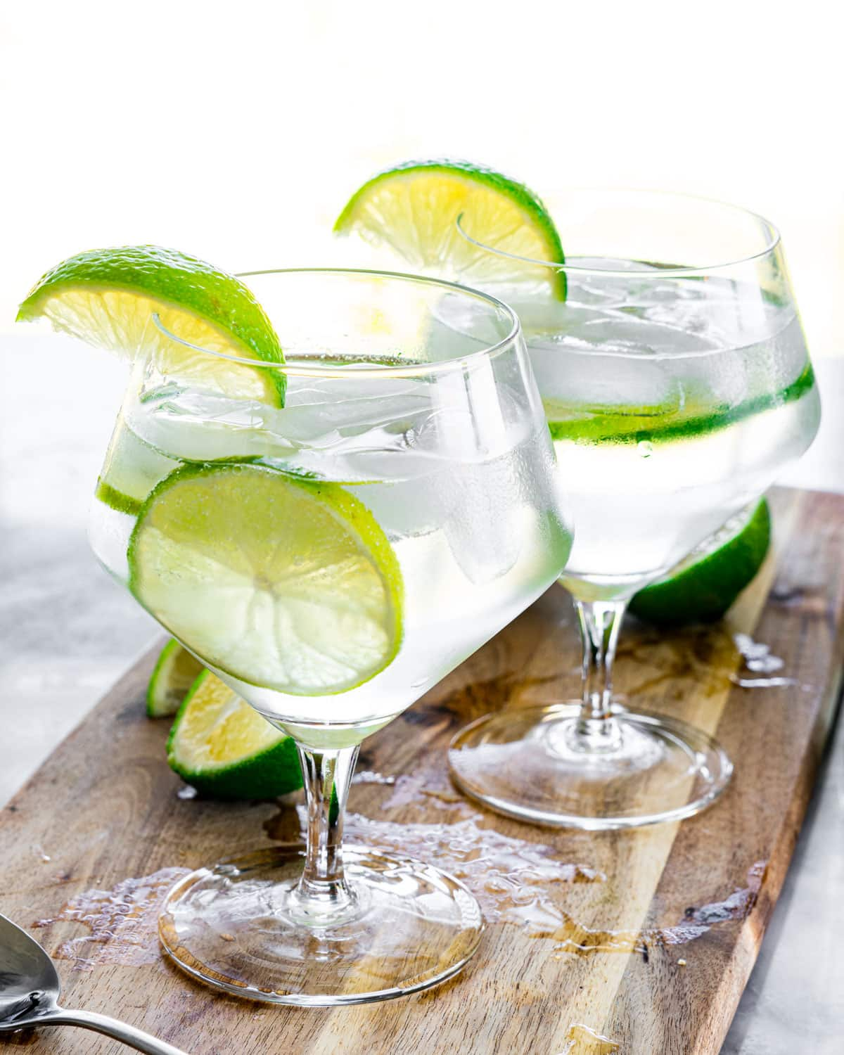 two gin and tonic glasses garnished with lime wedges on a cutting board