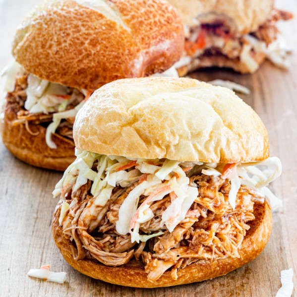 side view shot of a bbq pulled chicken sandwich with coleslaw on a cutting board