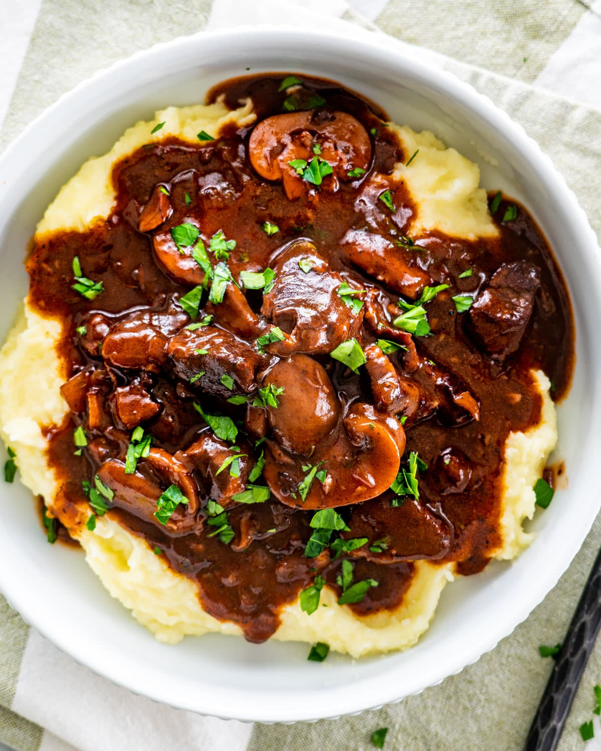 overhead shot of beef burgundy over a bed of mashed potatoes garnished with parsley in a white plate