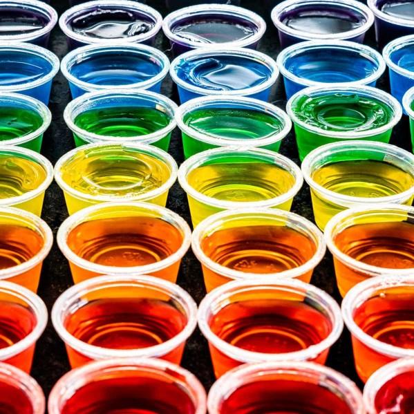 a rainbow of jello shots in small plastic cups