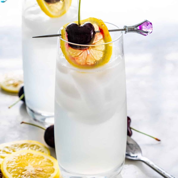 two glasses with tom collins garnished with lemon wheel and cherry