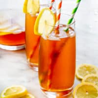 two glasses with boozy palmer arnold drink each with two straws in and lemon slice