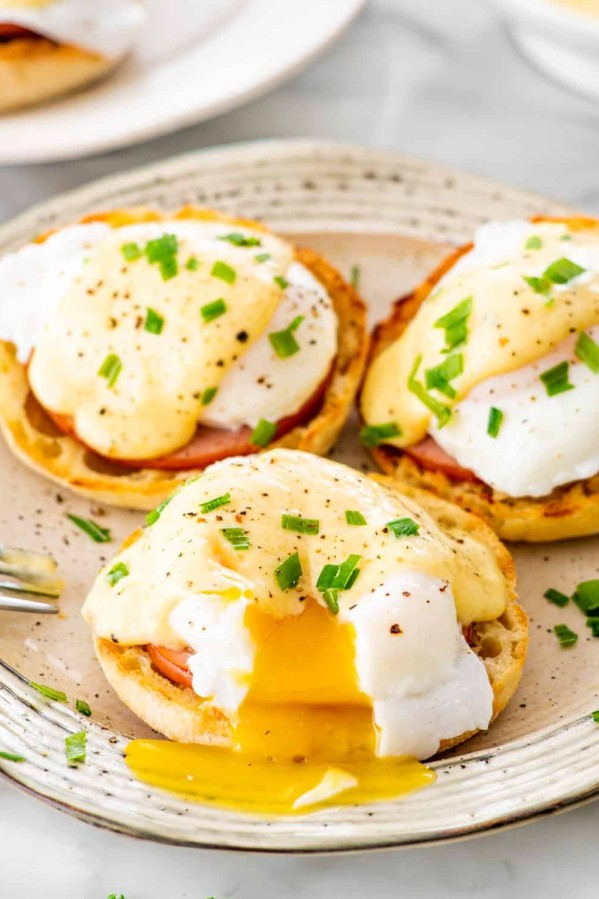 3 eggs benedict on a large plate garnished with chives