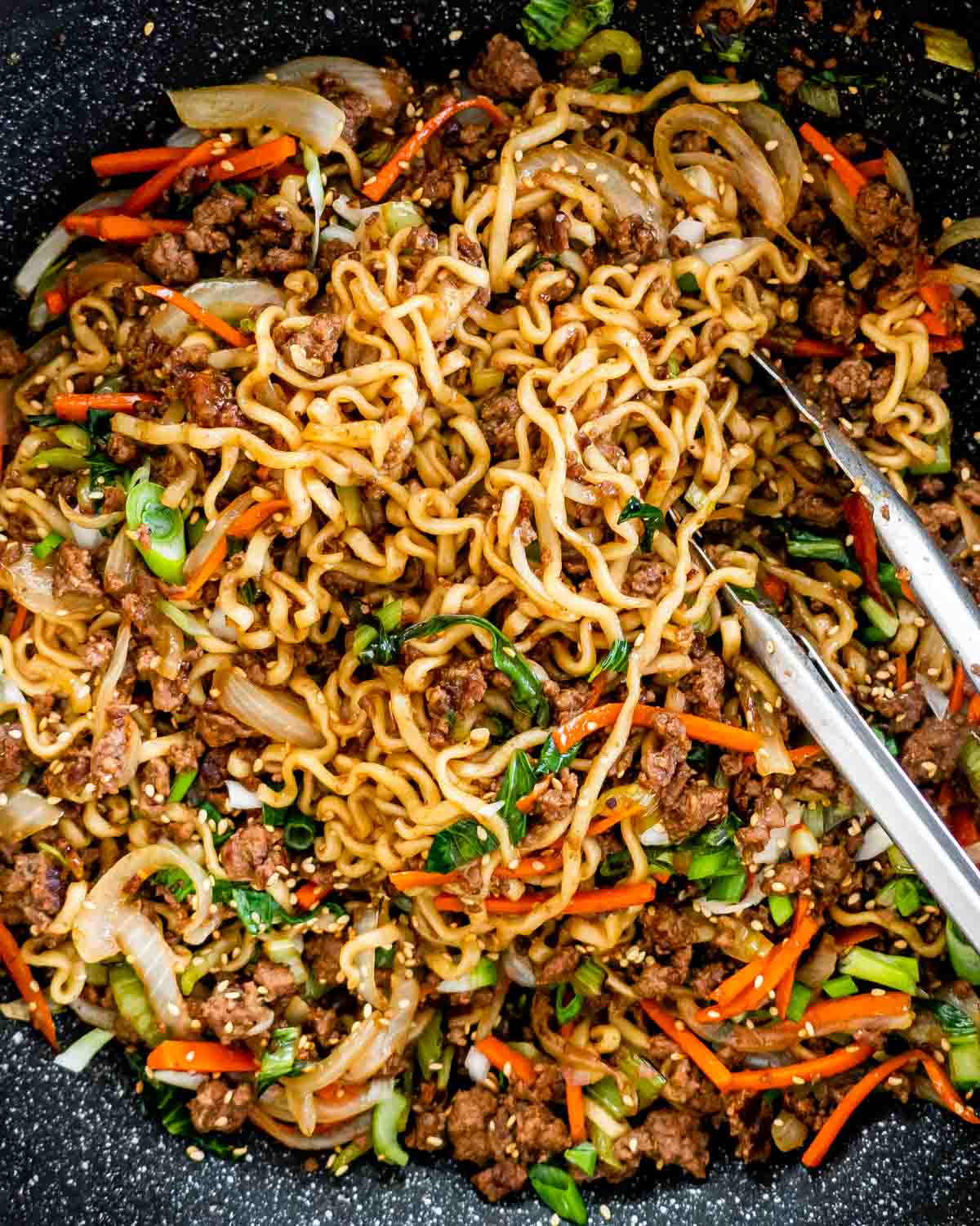 closeup overhead shot of hoisin beef noodles in a wok with a pair of tongs in it