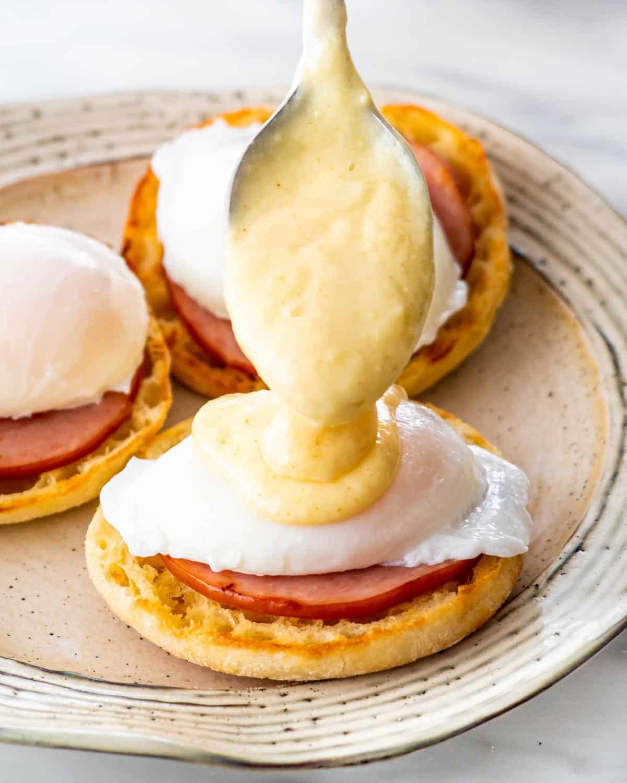 spooning hollandaise sauce over an egg benedict