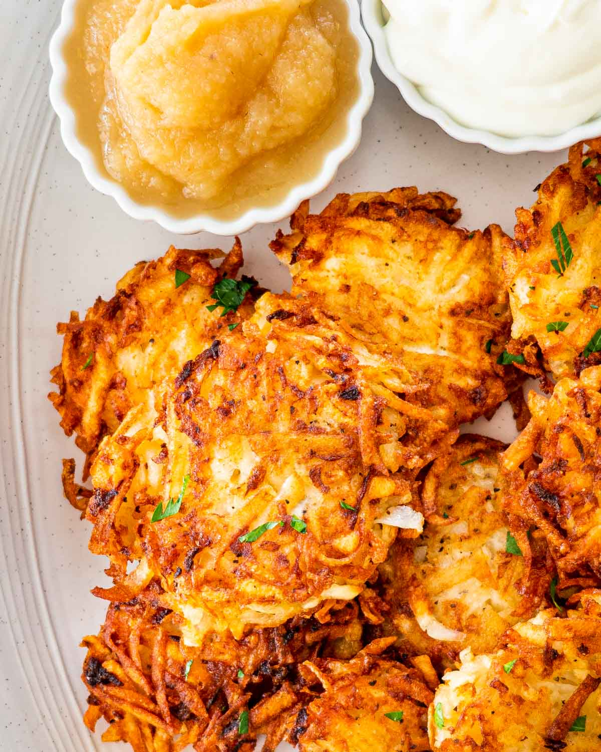 closeup shot of potato latkes on a serving platter with applesauce and sour cream