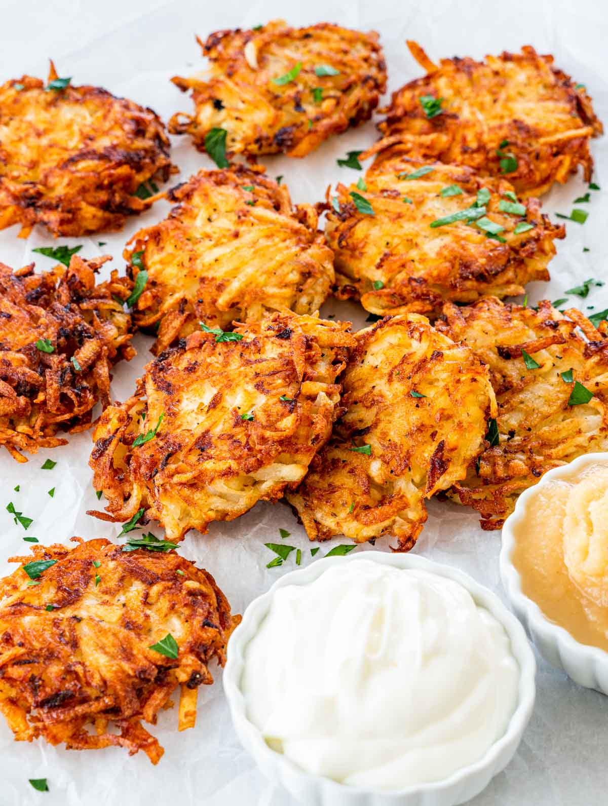potato latkes garnished with parsley next to two little bowls with sour cream and applesauce