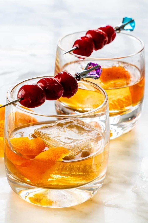 side view shot of two glasses of an old fashioned cocktail garnished with bourbon cherries on a pick and orange peel