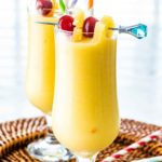 two glasses with Piña Colada and garnished with maraschino cherries and pineapple wedges