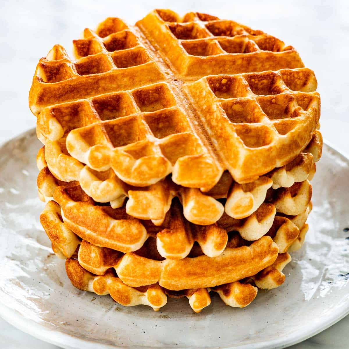 a stack of crispy belgian waffles on a white plate