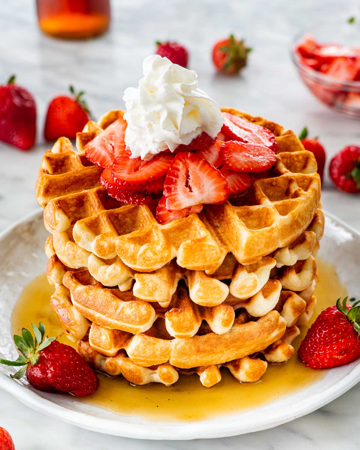 a stack of belgian waffles on a white plate topped with maple syrup, strawberries and whipped cream