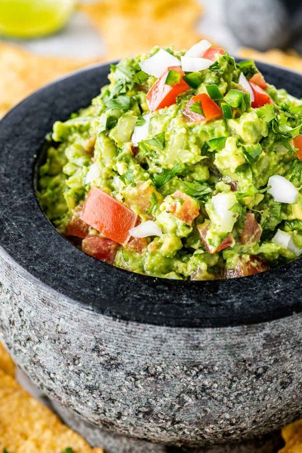 a stone bowl filled with freshly made guacamole surrounded by tortilla chips