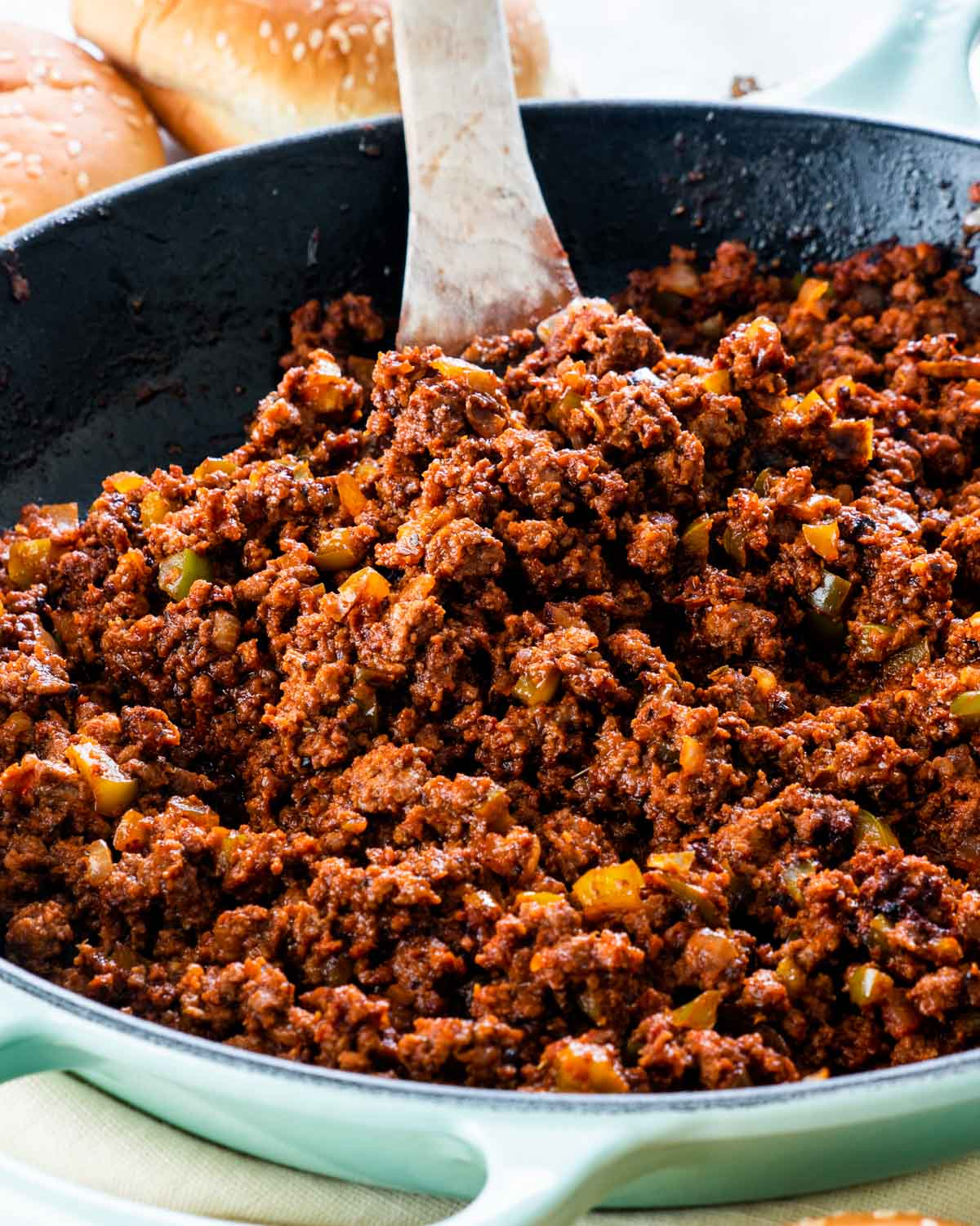 sideview shot of sloppy joe in a skillet with a spoon inside
