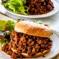 two plate with sloppy joes and buns next to a greens salad