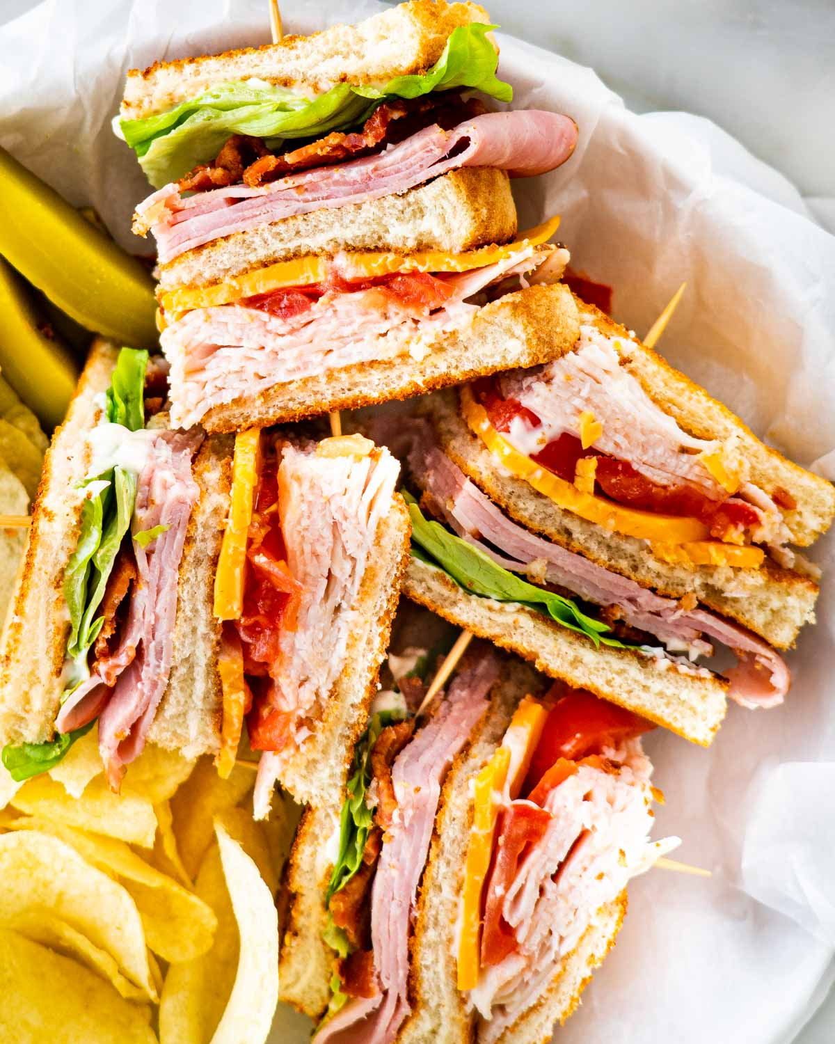 overhead of a club sandwich cut in quarters with a side of chips and pickles in a basket.