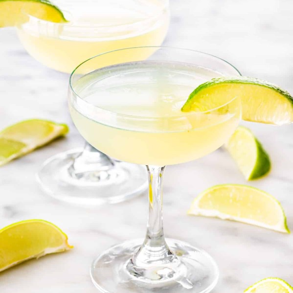 two glasses with daiquiri and garnished with lime wedges.