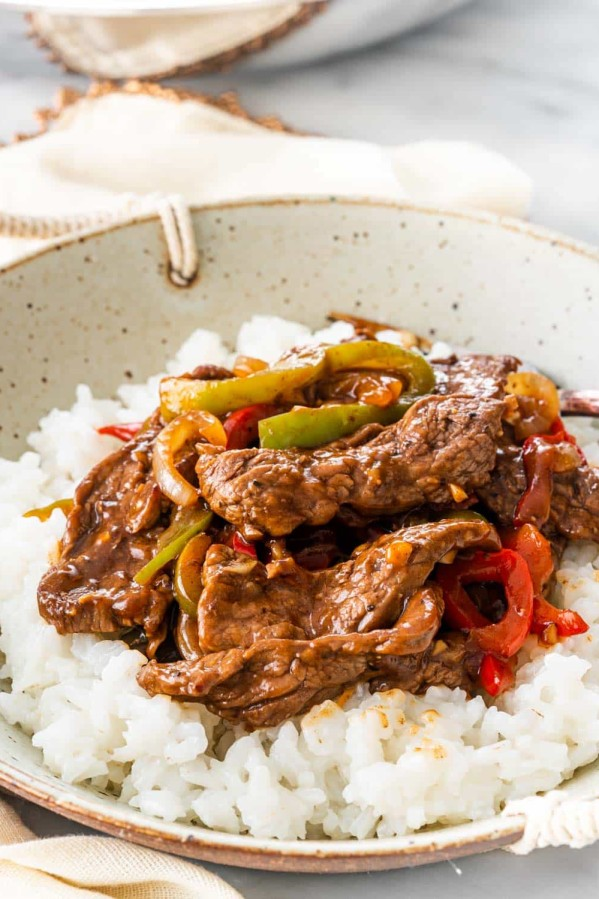 pepper steak over a bed of rice in a bowl