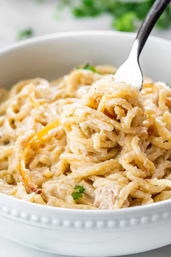 a fork twirling noodles in a bowl full of turkey tetrazzini.