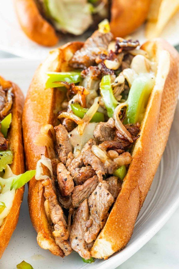 closeup of a philly cheesesteak sandwich on a white plate.