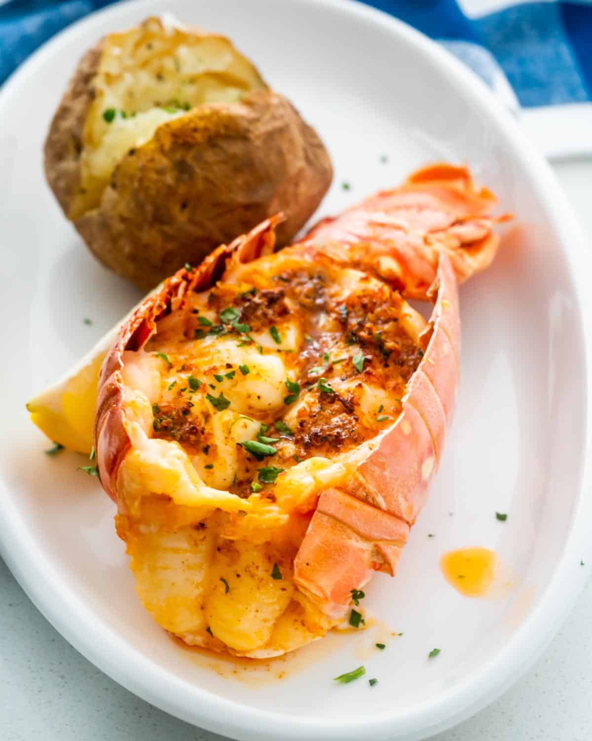 a lobster tail on a white plate with a baked potato.