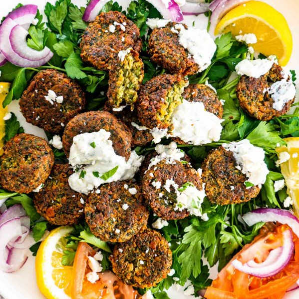 overhead of falafel on a plate with tzatziki, feta, tomatoes and onions.