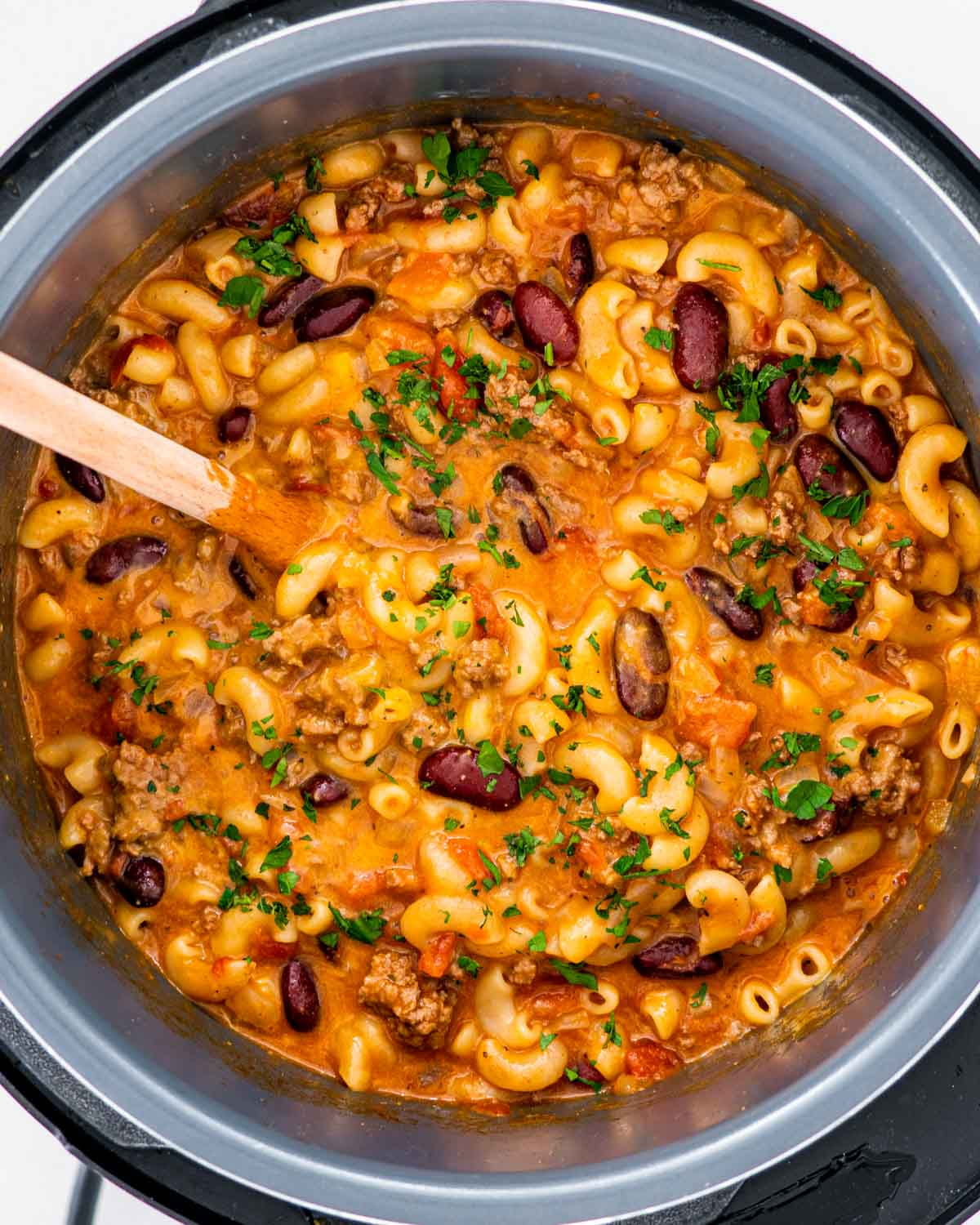 a large white bowl with freshly cooked chili mac with a serving spoon inside.