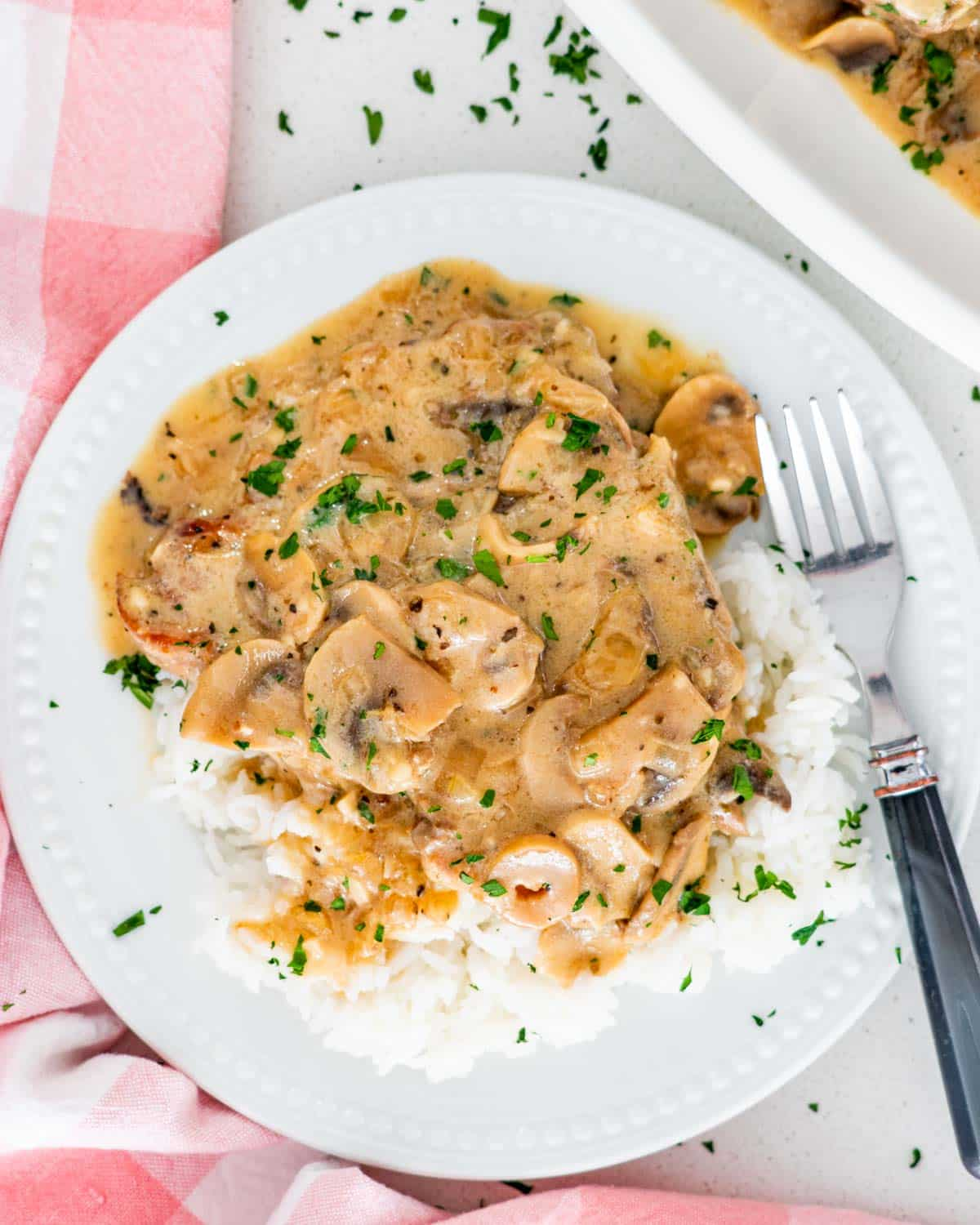 pork chops with mushroom gravy over a bed of rice on a white plate.