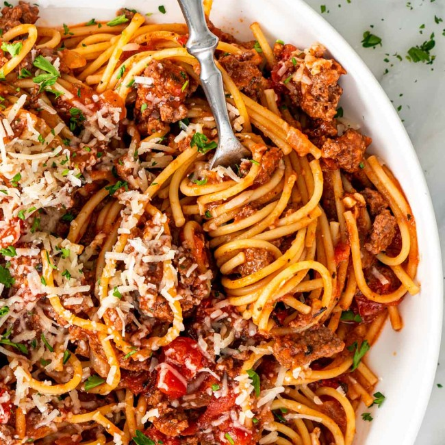 overhead shot of a fork with spaghetti twirled around it in a plate full of spaghetti.