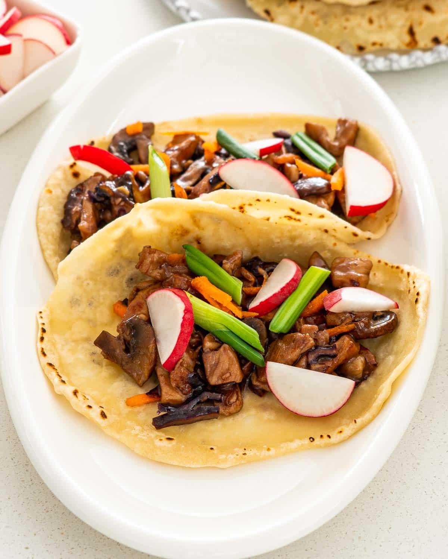 two mandarin pancakes on a white platter with moo shu pork.