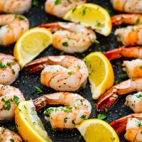 oven baked shrimp in a casserole dish with lemon wedges.