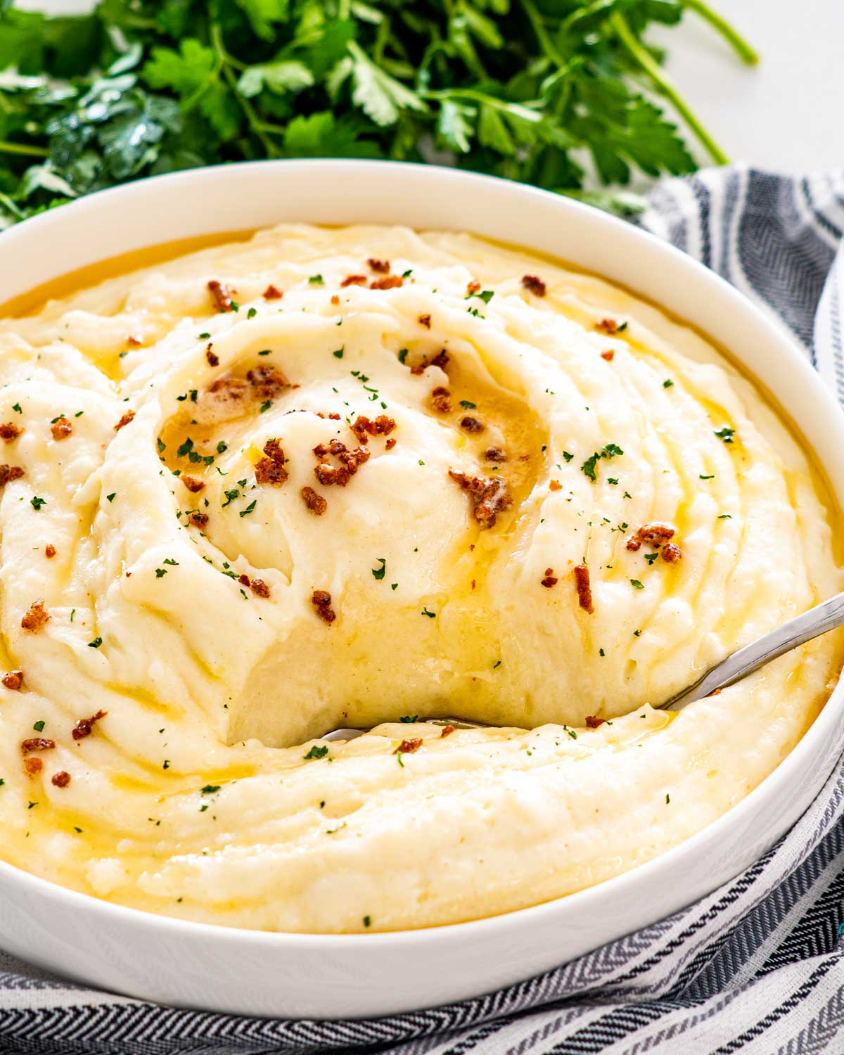 brown butter mashed potatoes in a big white bowl with a serving spoon inside.