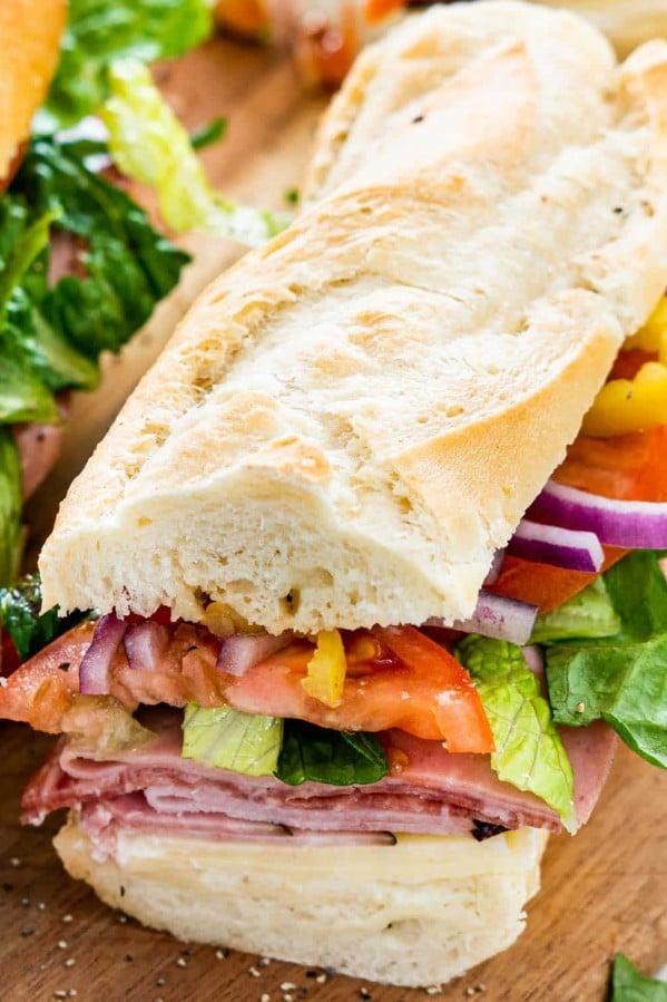 closeup of a freshly made italian sub on a cutting board.