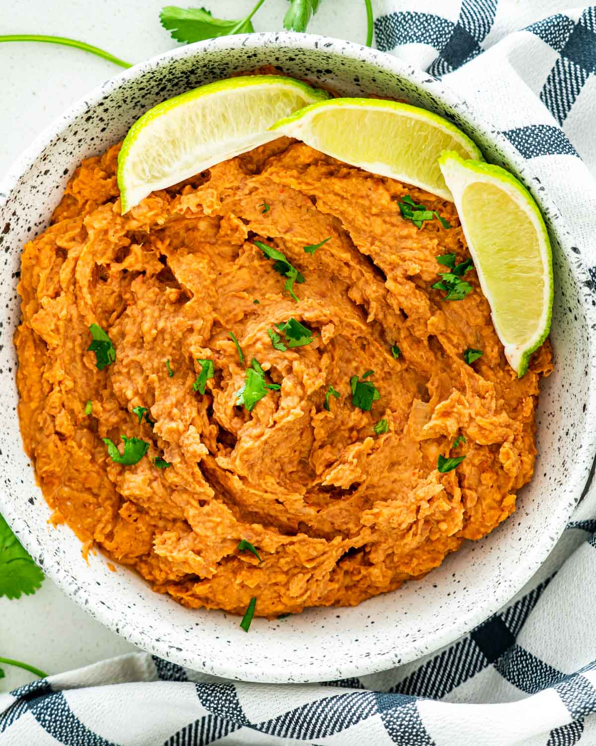 overhead shot of refried beans in a plate garnished with lime wedges and cilantro.