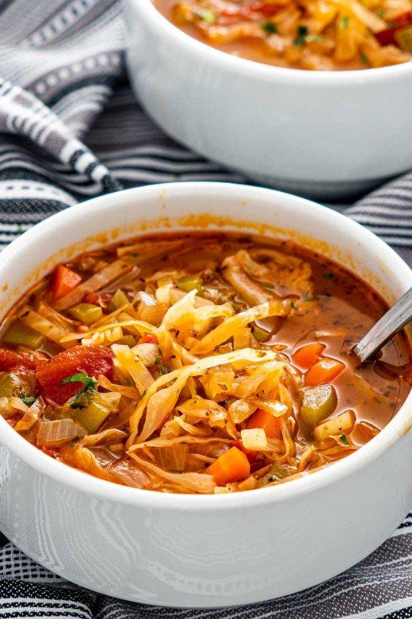 cabbage soup in a white bowl with a spoon inside.